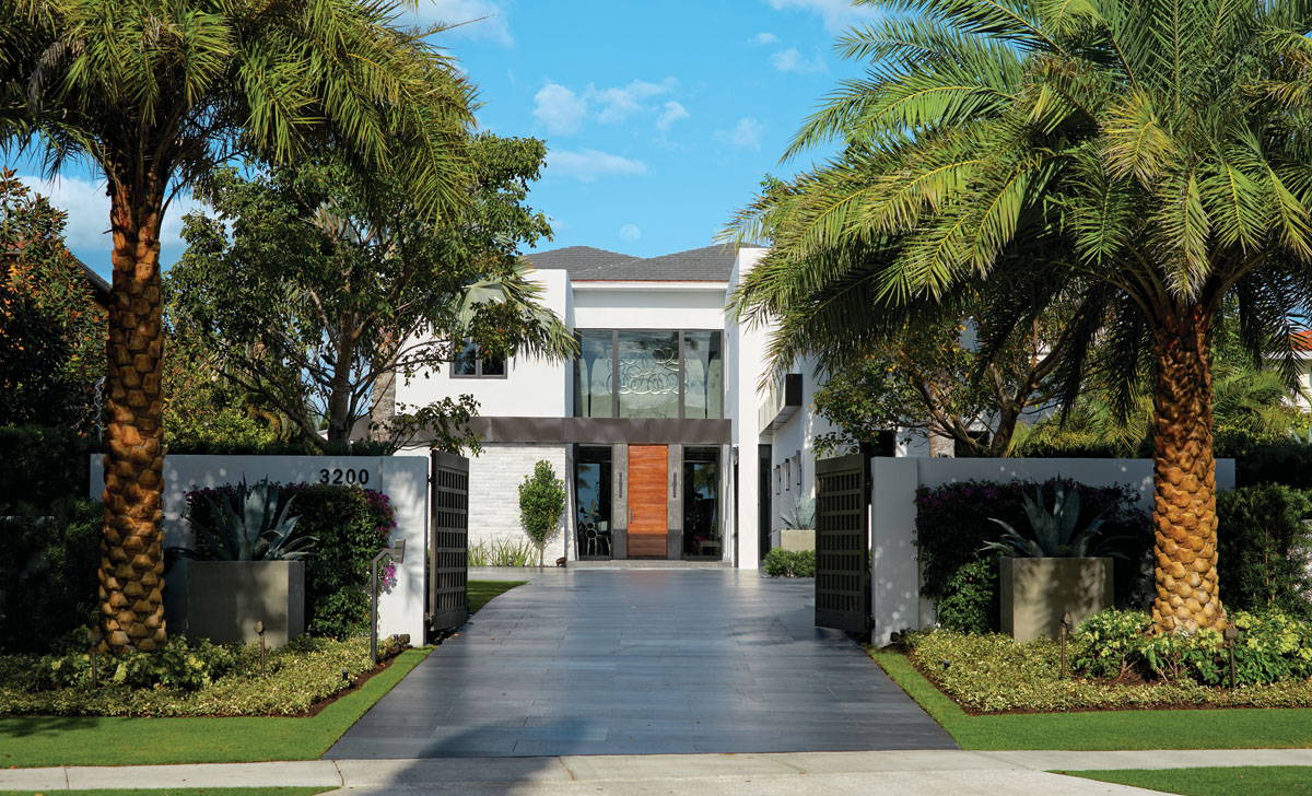 "Lined with palm trees and lush native plantings, the front entrance is punctuated with metal gates by Fowler Sheet Metal. A pair of Hinkley Lighting's ""Glacier"" wall sconces from PPM Collections styles the entry with a contemporary cool shape and an engaging contrast to the cypress wood door."