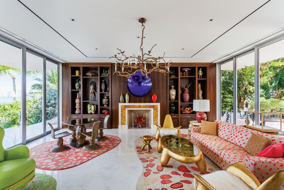 """American artist Liza Lou's flaming glass-beaded logs warm a 1940s Art Deco fireplace in the living room. Here, Claude Lalanne's bronze """"Lustre"""" chandelier branches out with soft candlestick lights, while gilded gold furnishings by Wendell Castle add energy and sheen. A custom sofa clad in Le Manach's colorful cotton, and like-minded wool and silk area rugs inject speckles of sherbet-shaded hues."""