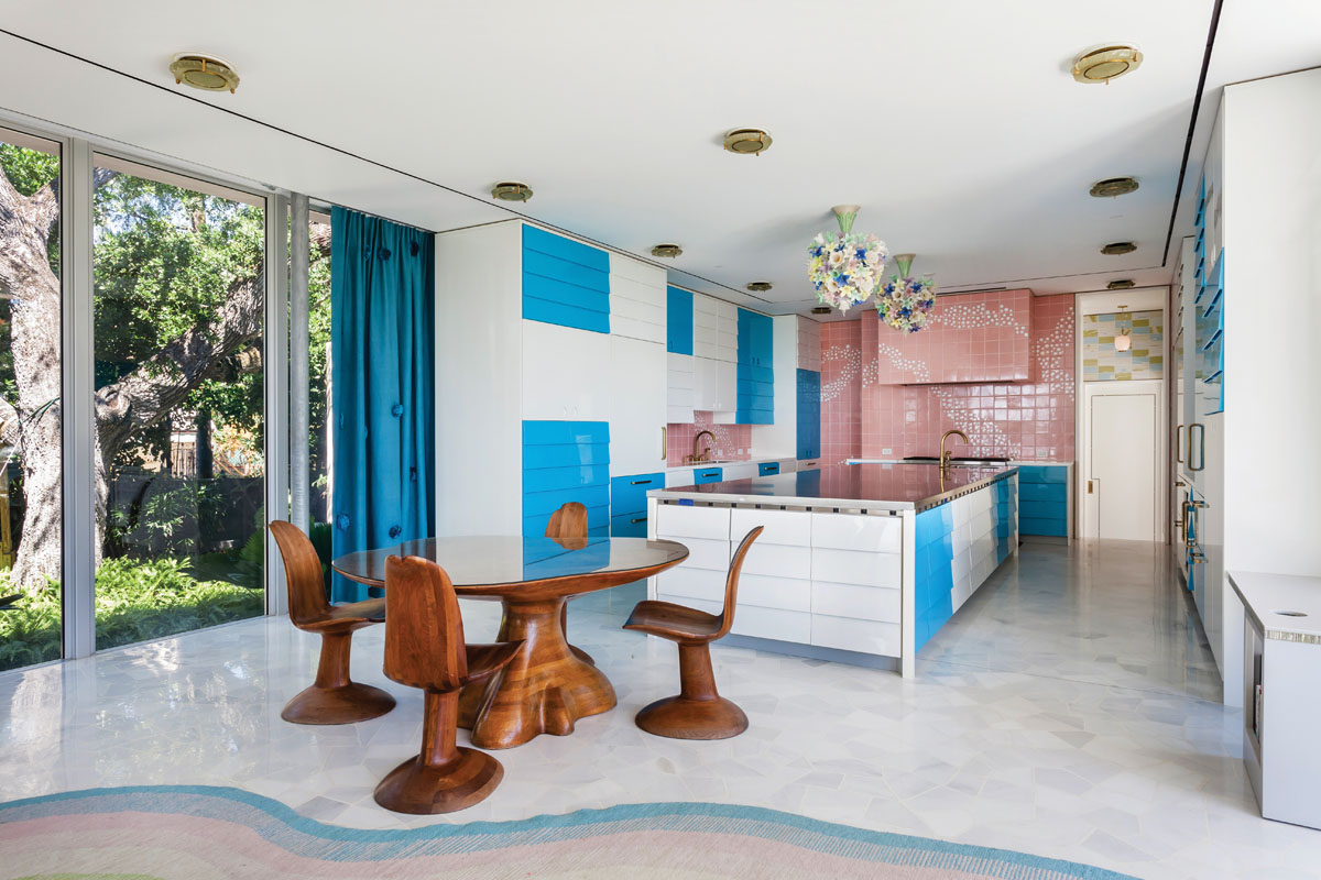"""Inspired by Gio Ponti, custom kitchen cabinetry features sharp blue and white contrast, stainless steel accents and clean lines. Mid-century """"Murano Flowers"""" chandeliers by Barovier & Toso, and Wendell Castle's carved-walnut table and chairs add an organic touch."""