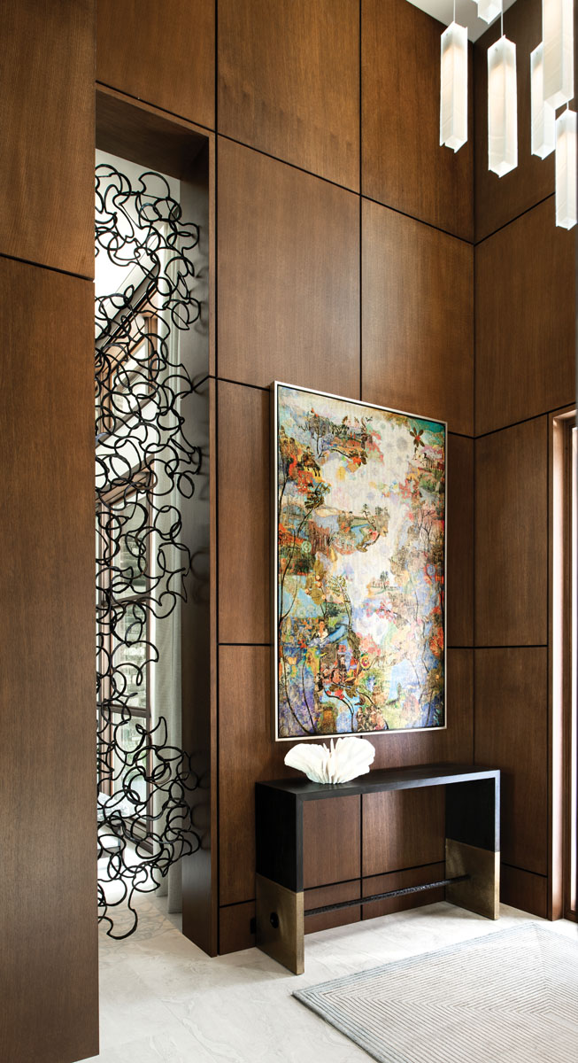 Just off the foyer, a collaboration with Qui Studios resulted in the organically shaped, custom metal screen — individual linked circlets the artisans installed a piece at a time. Artist Suzy Scarborough's Voyage Past the Future colors the wall above an Arteriors console.