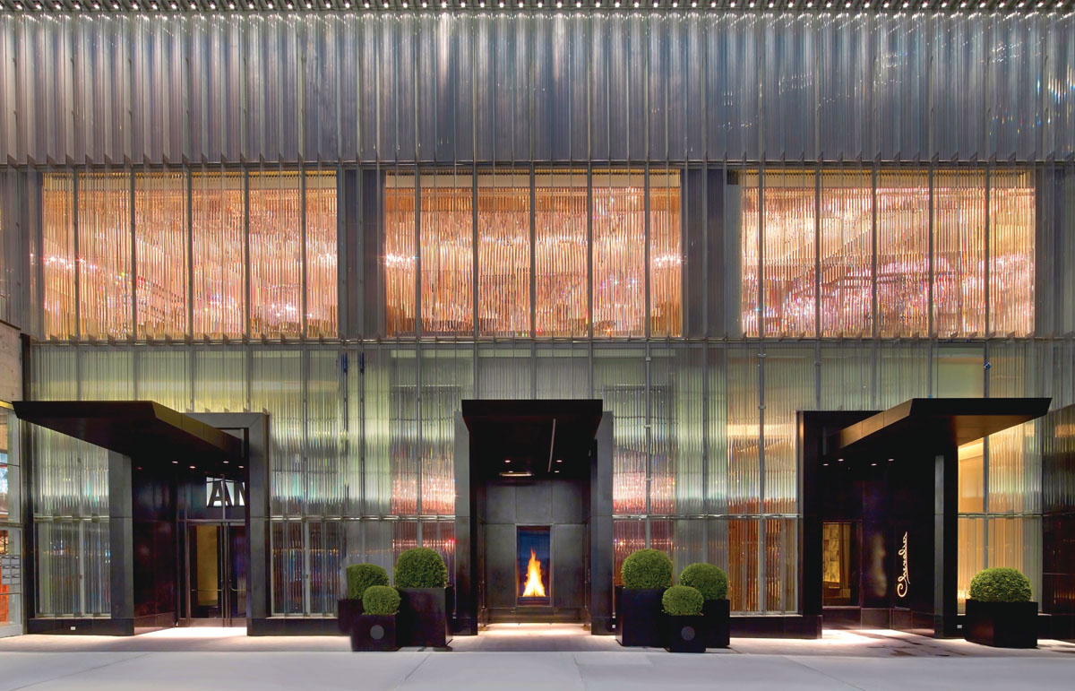 Baccarat Hotel New York's design fashions a simple exterior with great drama added via a corrugated crystal-like curtain and a four-foot-high, always-burning fireplace that welcomes guests.