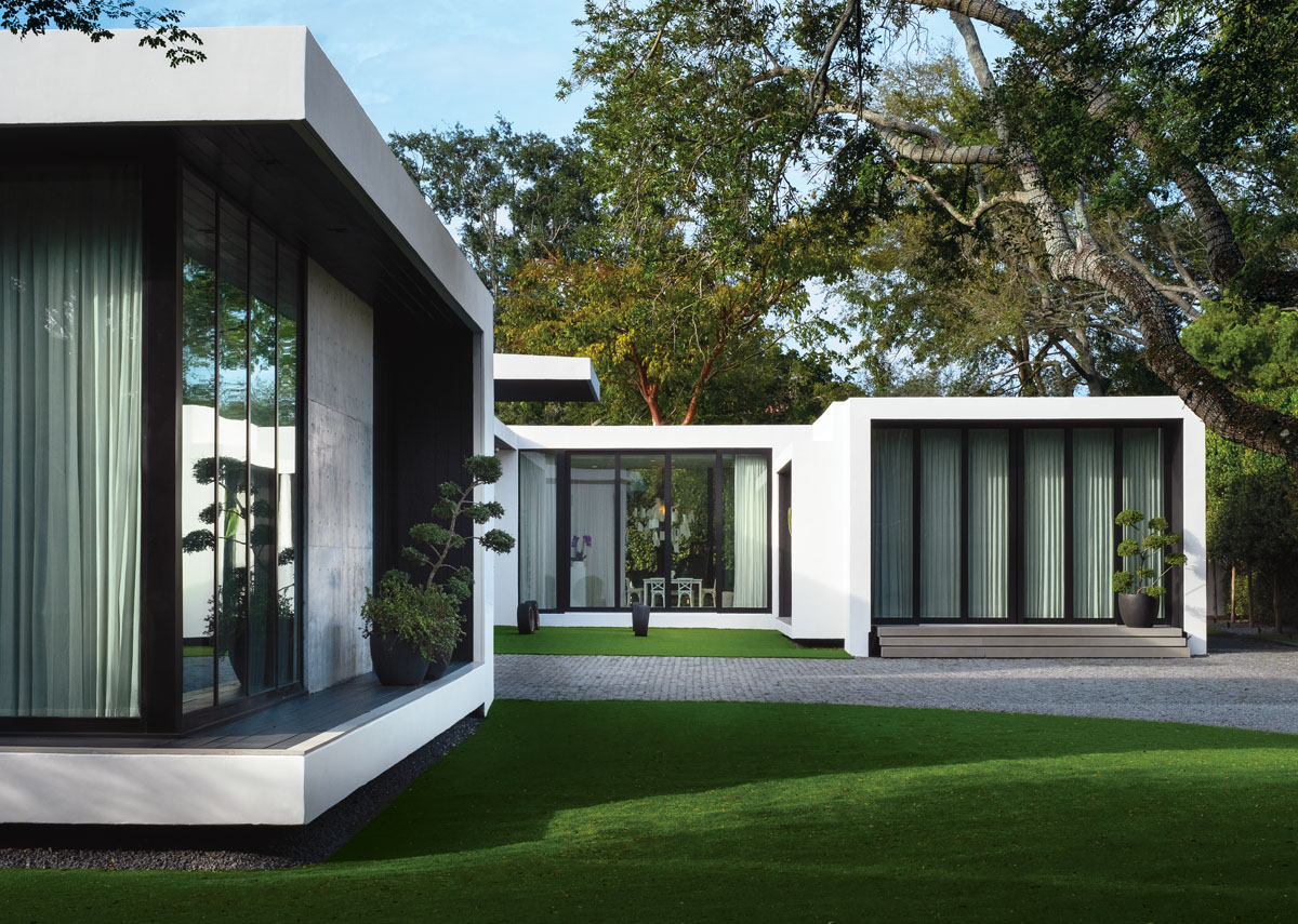 "Graceful live oaks frame the geometric lines of this ""tropical modern"" home. Concrete slabs step up to Alex's private office that is seamlessly connected to the home via glass sliders that open to a central courtyard."