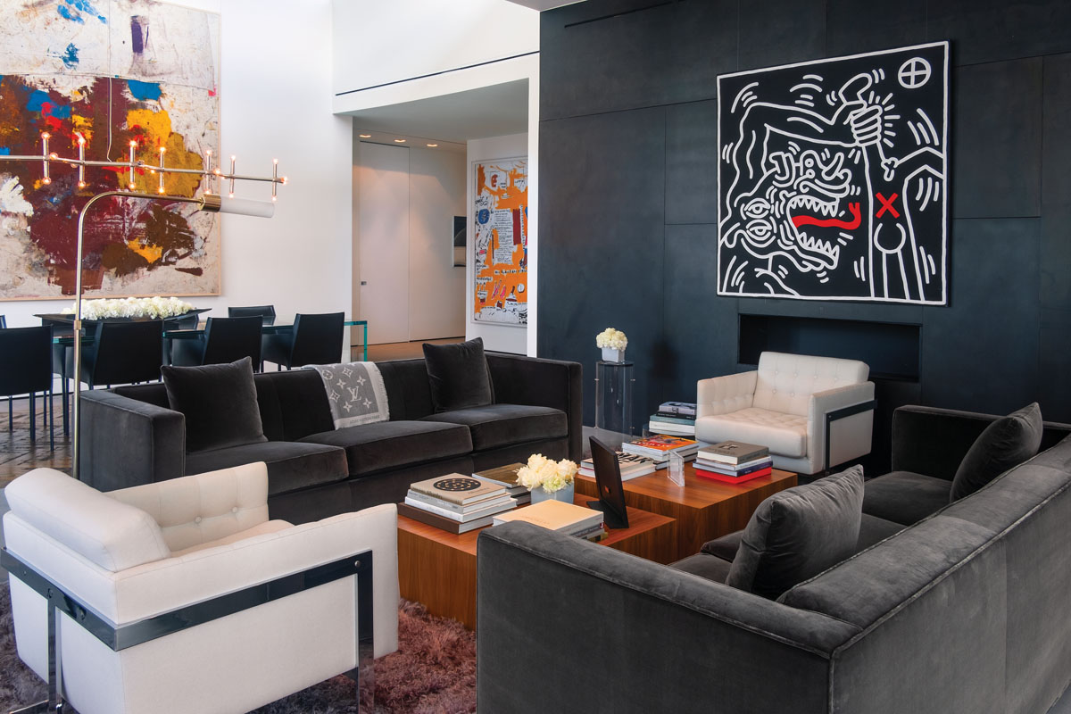 Blackened-steel panels make a handsome backdrop for a Keith Haring painting above the linear fireplace. Hearthside, interior designer Briggs Edward Solomon paired vintage cantilevered Milo Baughman lounge chairs in a Holland & Sherry cashmere with three-seater sofas upholstered in a cotton velvet from Brunschwig & Fils. A portrait of Jean-Michel Basquiat by Andy Warhol catches the eye on one side of the living area, while a piece by the famed Basquiat himself peeks out from the hall on the other.