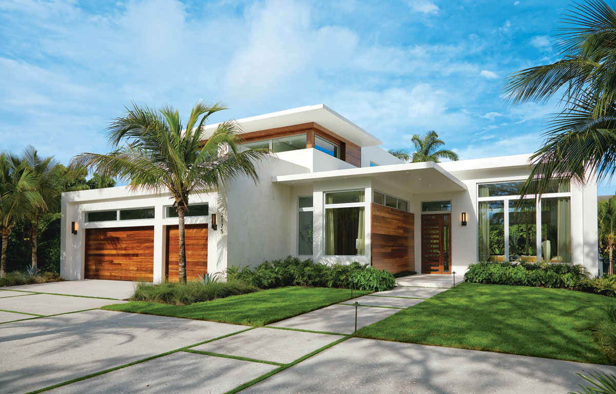 Ipe wood styles this two-story tropical modern home in Naples with a beautiful garage door, accent wall and stunning entry door. Modern Forms' sconces capture the architectural essence.