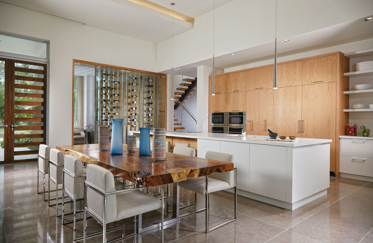 The custom Nicaraguan wood dining table contrasts with the chrome-framed, white linen-upholstered chairs from Palecek. Decorative vessels in blue and earthy tones complement the organic interior scheme. Contemporary light pendants and Allikriste's kitchen cabinetry add grace and refinement to the open space.