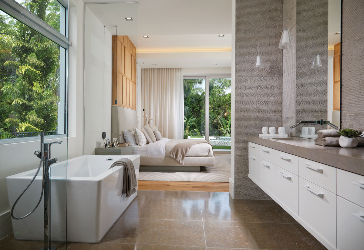 "A chiseled limestone tile wall provides an organic feel in the luxurious master bath designed with a polished limestone countertop and flooring. His-and-her sinks set within an Allikriste vanity and a deep-soak tub are equipped with contemporary Hansgrohe faucets. ""All of the architectural lines in this space are strong and square like the house,"" interior designer Jason Lynn says."