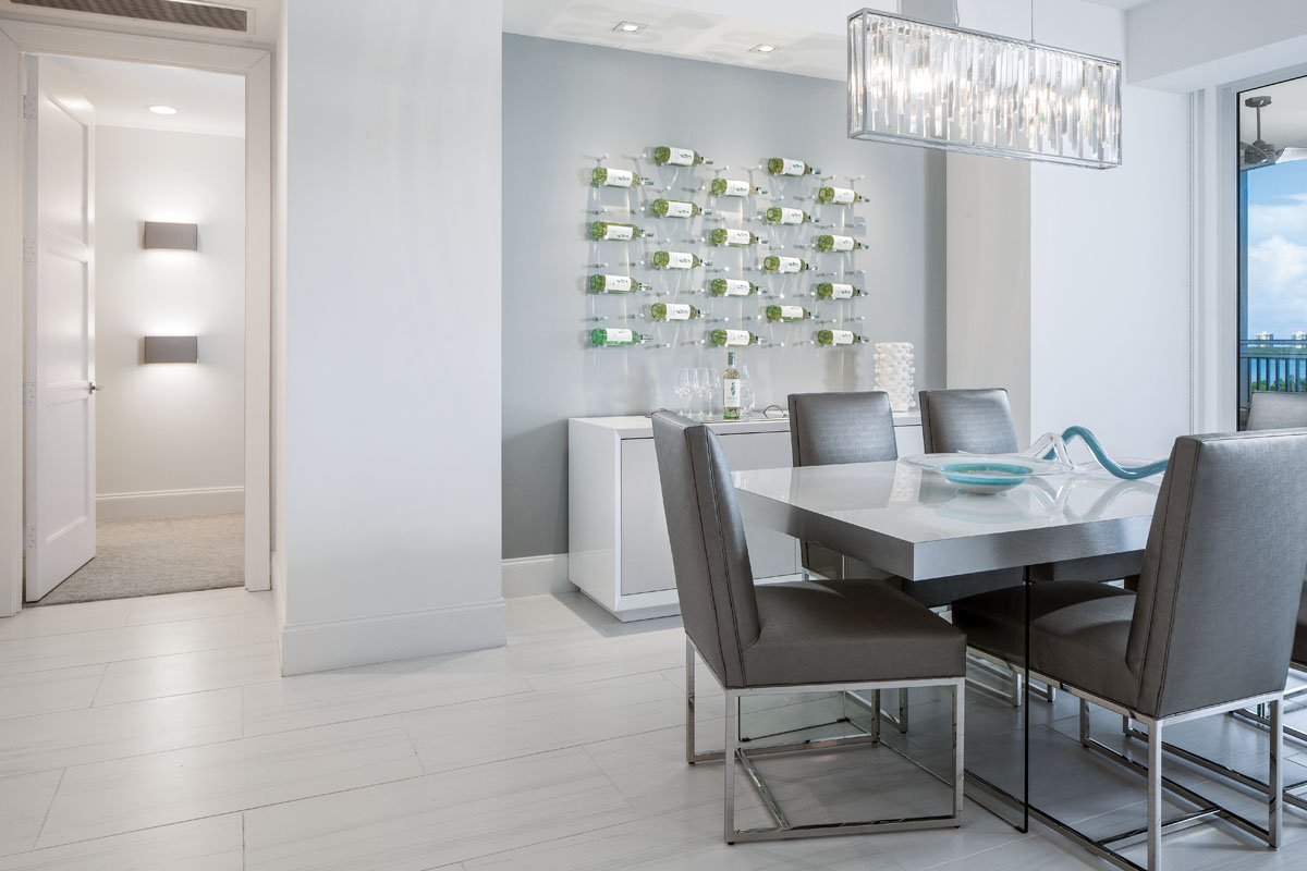 The designers created a unique wine wall and serving bar in the dining room, where Eurofase's chandelier separates white light into a spectrum of color above a custom, silver laminate table and Vanguard's chairs styled in vegan leather.