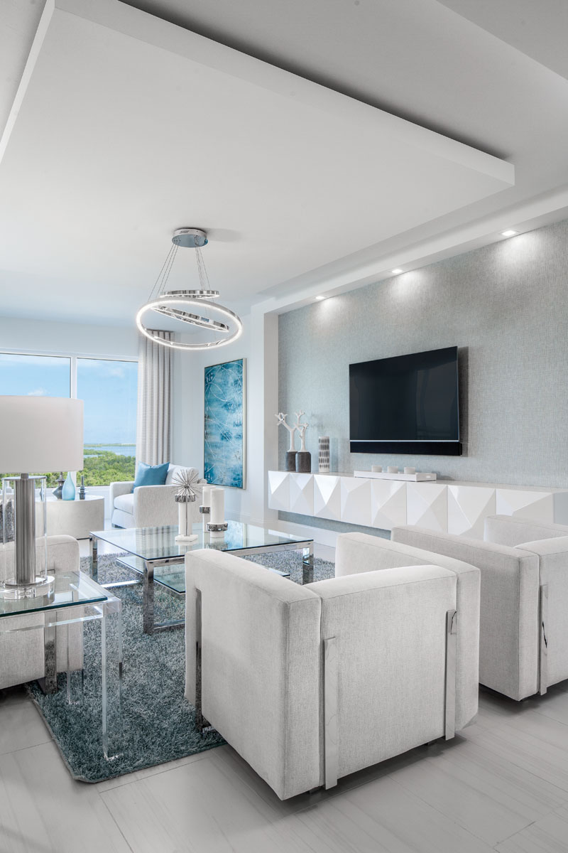 """A custom, white-lacquer floating console lines the wall in the living room. Elan's polished chrome chandelier styled with three LED bracelets of concentric sizes appears to dance above Sunpan's seating centered by Bernhardt's glass-topped cocktail table. """"The blue painting, Rhapsody, matches the beauty of the outdoor views,"""" interior designer Elizabeth Manchego says."""