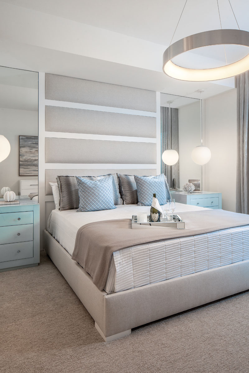 """A custom, upholstered headboard wall provides a focal point in the master bedroom, where spa-blue painted bedside chests from Worlds Away are reminiscent of sea glass. """"WAC Lighting's """"Corso"""" chandelier became the jewel of the room like a bracelet,"""" Manchego says."""