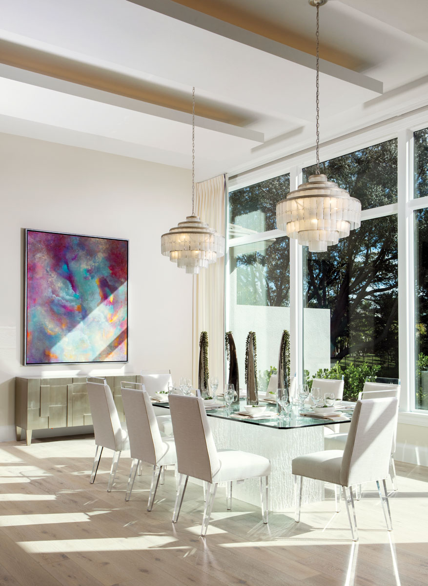 """Framed windows capture picturesque views from the dining room, where a pair of Currey & Company chandeliers shimmers above Bernhardt's glass-topped table with its """"Artic"""" base. Design Master's """"Hollywood"""" chairs sparkle and shine with acrylic top rails and tapered legs, while a painting commissioned by a local artist creates colorful contrast."""