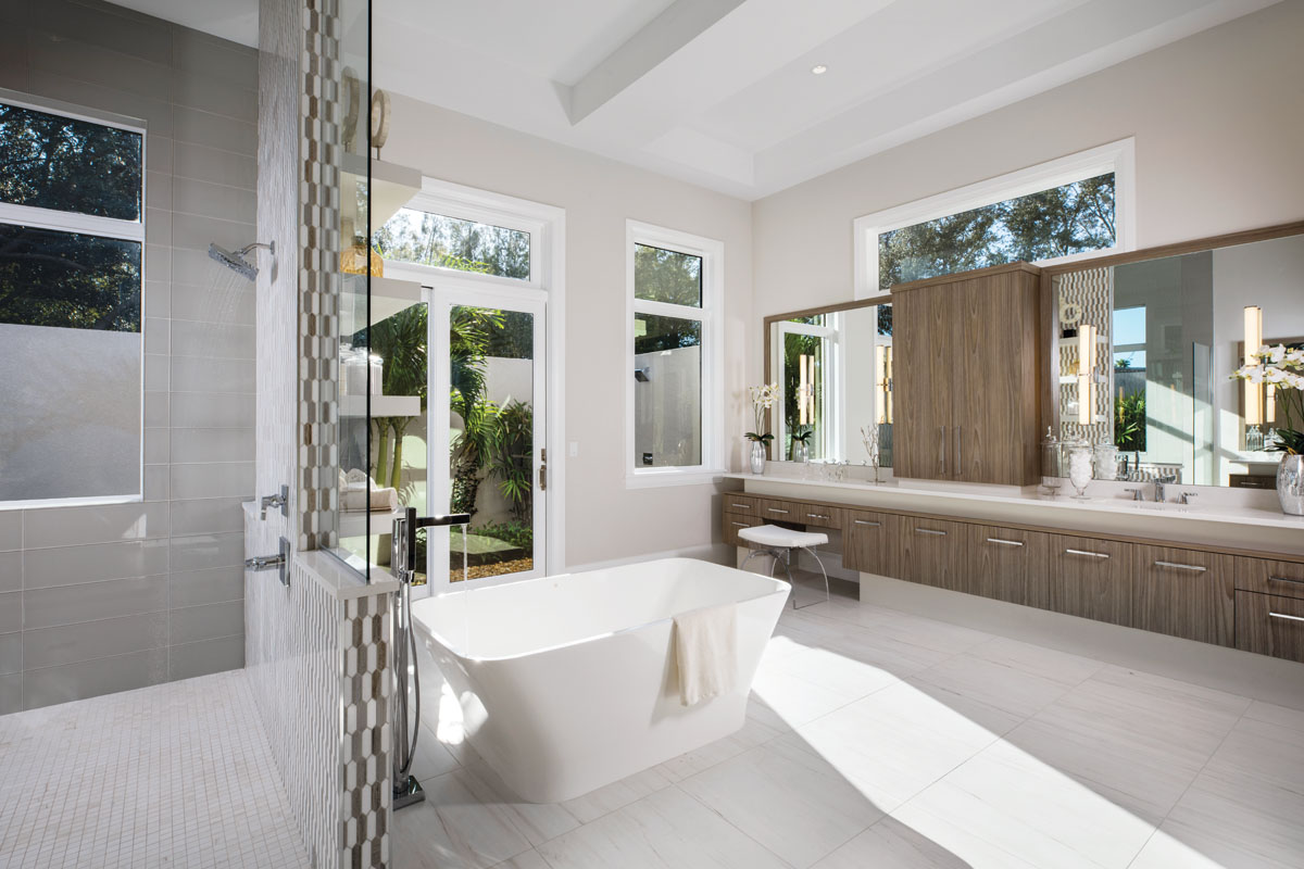 Styled in stained linear oak topped in contrasting white marble, the spa-inspired master bath boasts an inviting freestanding tub from Ferguson and access to a private courtyard beyond. A contemporary stool from Worlds Away pulls up to the luxuriously long vanity embellished with Yochman vanity lights.