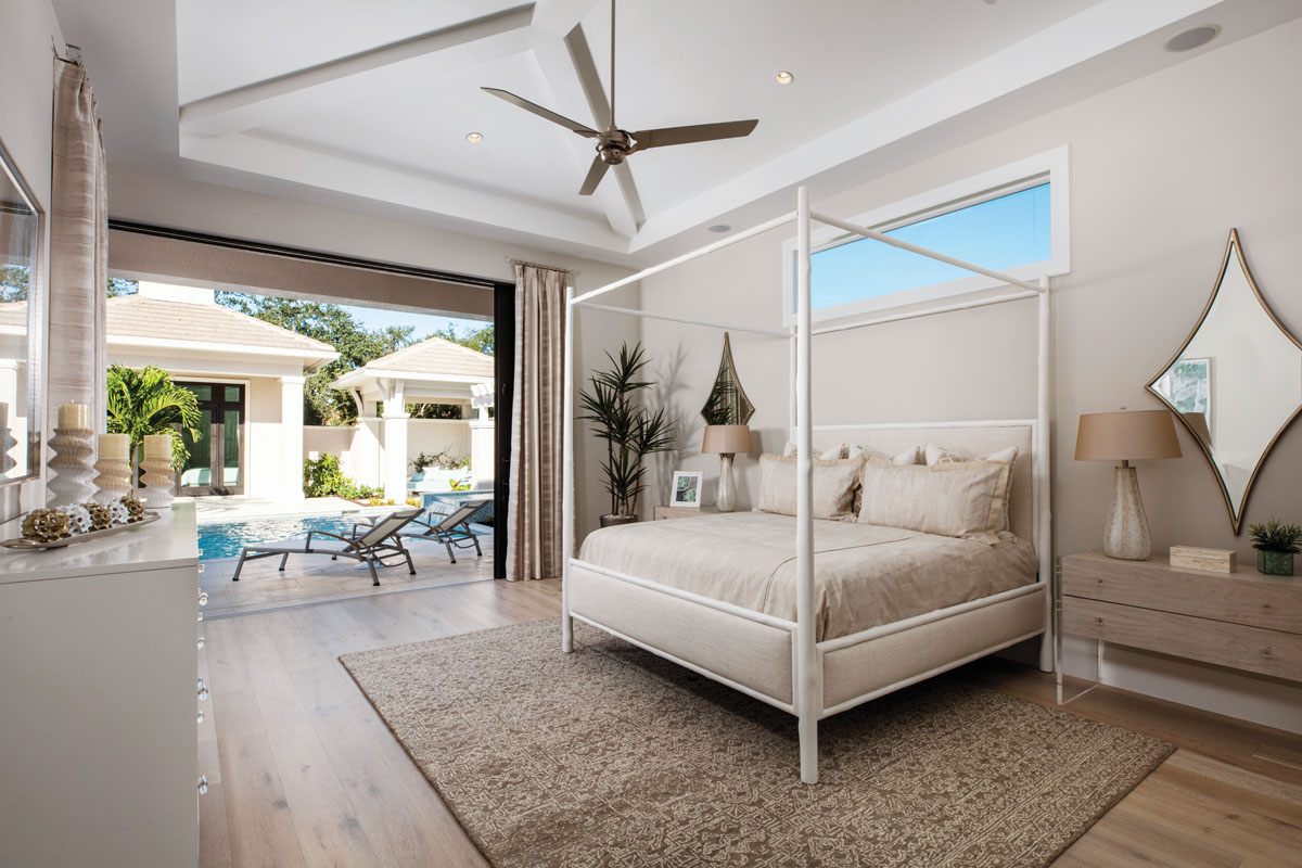 Bathed in serene shades of sand and white, the master bedroom visually connects to the courtyard and pool to exude a light and restful feel. The four-poster bed is flanked by floating acrylic and wood bedside chests, all by Bernhardt. A woven area rug from Surya lends softness underfoot.