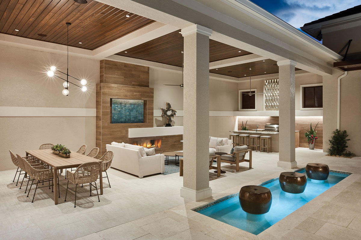 The adjacent living area's feature wall incorporates an asymmetrical design with a linear fireplace and inset television above. Here, a teak sculpture from Phillips Collection creates a captivating focal point, while an intimate grouping sits around the poolside fire pit.