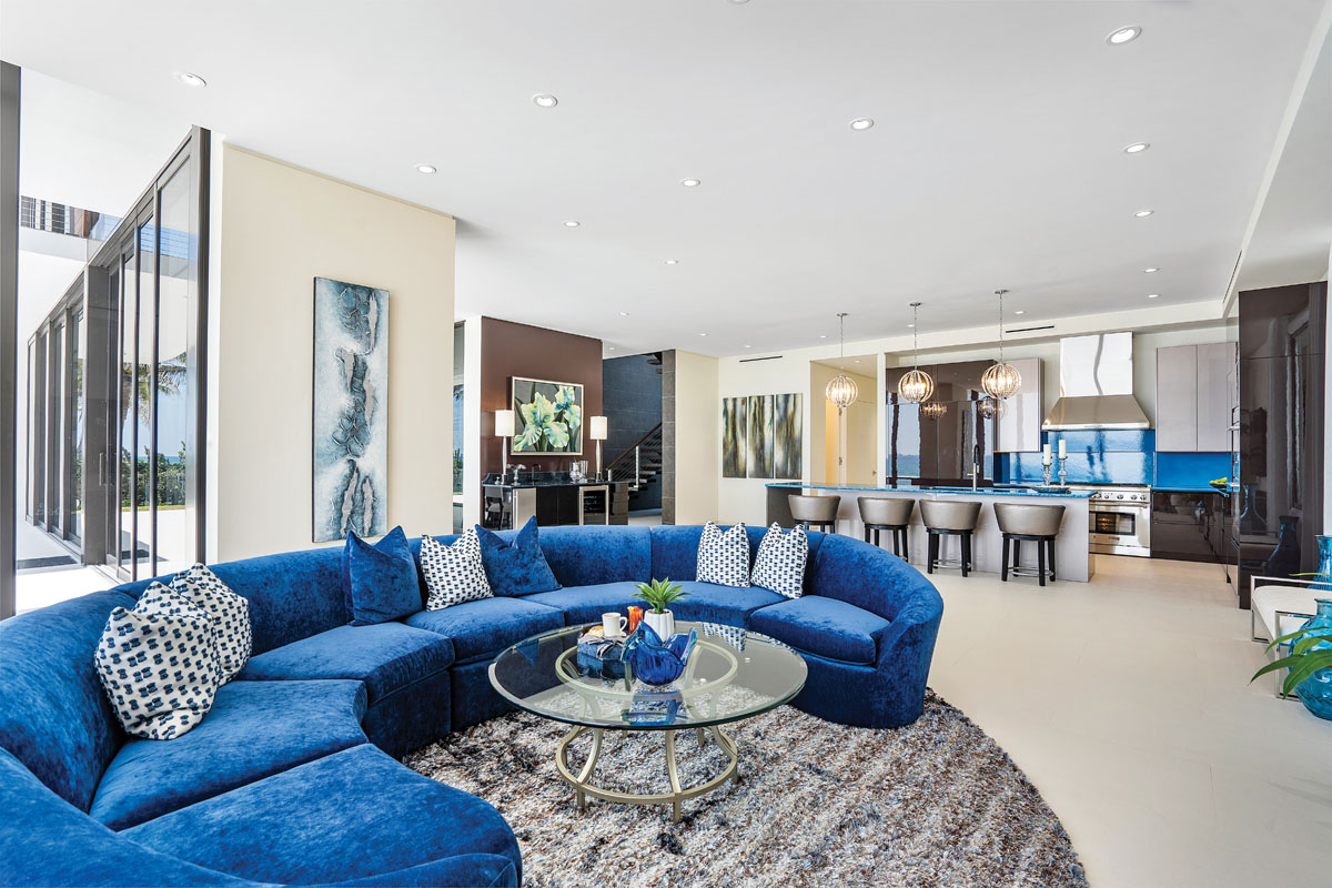 With walls of glass that completely disappear to expose the oceanfront deck, the family room is a gem fashioned with Century's sinuous sofa wrapped in a blue velvet and cotton blend. Sit on one end and you're looking at the ocean, sit on the other and you're facing the kitchen — a favorite gathering spot in the heart of the home.