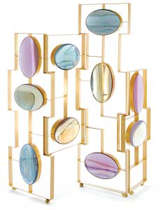 "Framed in brass, the limited-edition ""Aurora"" folding screen by Mccollin Bryan is colored in jewel-toned oval resin. mccollinbryan.com"