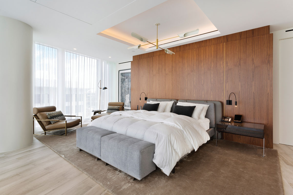 """Custom walnut wall panels provide a warm backdrop for the Minotti bed and bedside chests in the master bedroom. Thayer Coggin's """"Cruisin'"""" lounge chairs, one of Milo Baughman's iconic midcentury modern masterpieces, shapes a cozy sitting area. """"Our process to design takes 'living well' to a higher level by never losing sight of the significance of natural light,"""" Chin says."""