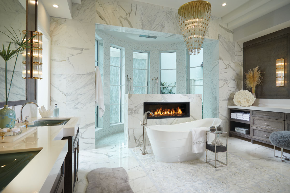 """In the master bath, a light-filled shower surround lines the turret's curves with thousands of mother-of-pearl tiles. Ferguson's freestanding Wyndham soaking tub takes center stage along with a linear, gas fireplace and a marble, abstract mosaic floor runner. Wall sconces by Ralph Lauren glow above the silver-gray bird's eye maple vanity topped in slabs of quartzite, while shimmering light dances from Circa's hand-rubbed, antique brass """"Mia"""" chandelier."""