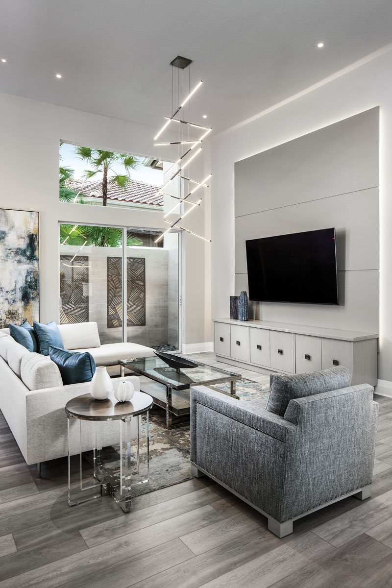 """The family room's social grouping is inviting with a beige sectional sofa from Thayer Coggin; a deep-seated lounge chair; a wood, metal and glass cocktail table; and a Lucite occasional table, all by Vanguard. The """"Tik-Tak"""" stacked pendant light by Sonneman creates a nested feel."""