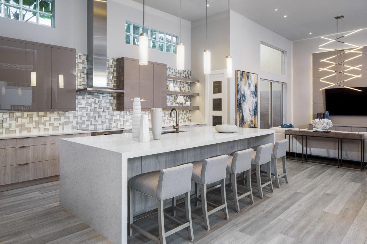 """Separating the kitchen from the family room, low-profile counter stools tuck neatly beneath a large, 11.5-foot-long waterfall-edge island shaped of sparkling Pompeii quartz. """"The windows dictated the symmetry of the space, and we worked with the contractor to make sure that we scaled the island appropriately,"""" interior designer Laurie Walter says."""