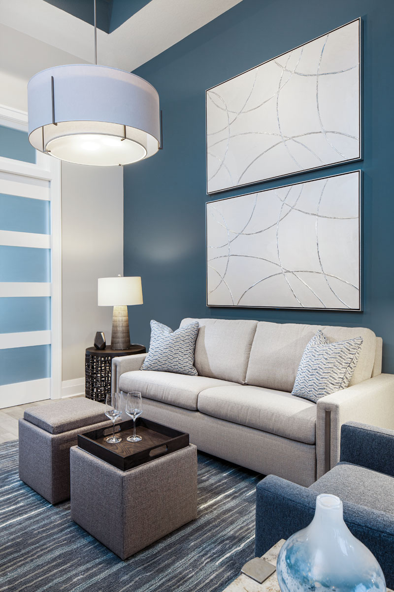 """Furnished with an American Leather sleeper sofa and nesting cocktail tables with flip trays that provide storage for bedding, the den doubles as a guest room. Here, Silver Strands by artist Lupita Denogeán provides an artistic focal point, while the """"Exos"""" double shade pendant from Hubbardton Forge casts circles of light around the space."""