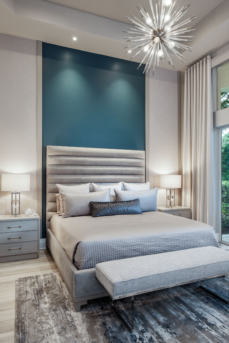 """Adding a touch of drama, the master bedroom is lighted by the """"Andromeda"""" starburst pendant from Wilson Lighting. An acrylic and polished-chrome Bernhardt bench covered in faux linen rests at the foot of Vanguard's upholstered bed."""