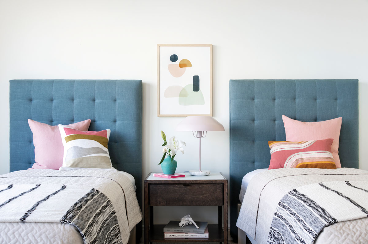 Pretty in pastels and just perfect for grandchildren, one guest room is styled with custom twin beds outfitted with linen-tufted headboards in a dusty aqua hue. A Huppé single-drawer, birch bedside table provides the perfect spot to hide secret treasures discovered during the day's adventures.