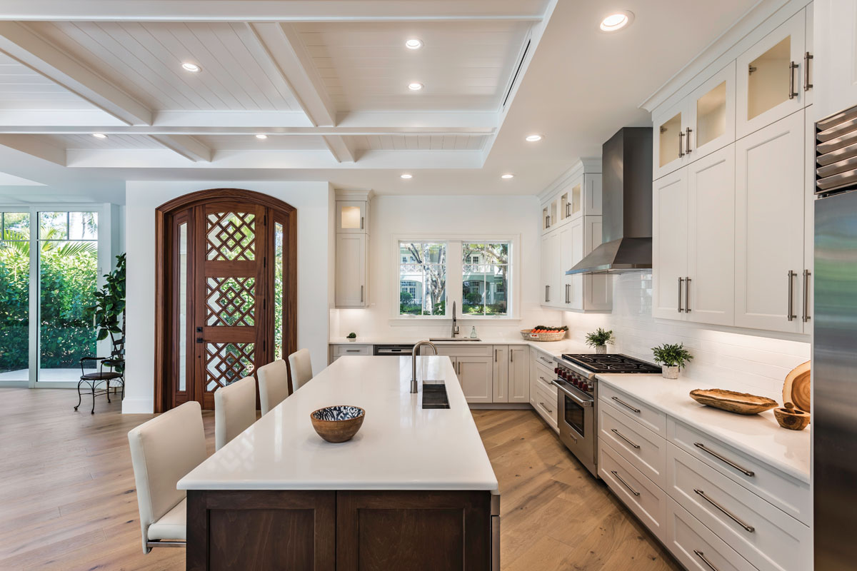 In a coastal-inspired white palette, the spacious kitchen includes an expansive island that provides seating for four and plenty of room for food preparation. White oak flooring and an elegant front door finished in a dark wood stain create visually compelling contrast and bring an element of rusticity to the space.