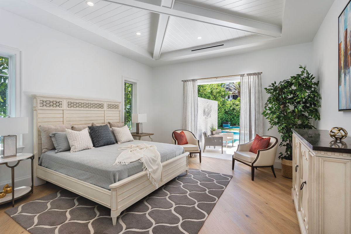 The spacious, first-floor master suite opens onto the pool area and successfully blurs the lines between inside and out. A white, custom-designed beamed ceiling brings a beachy feel to the space and provides a beautiful backdrop for the earthy tones of the furnishings and the plush area rug that anchors the space.