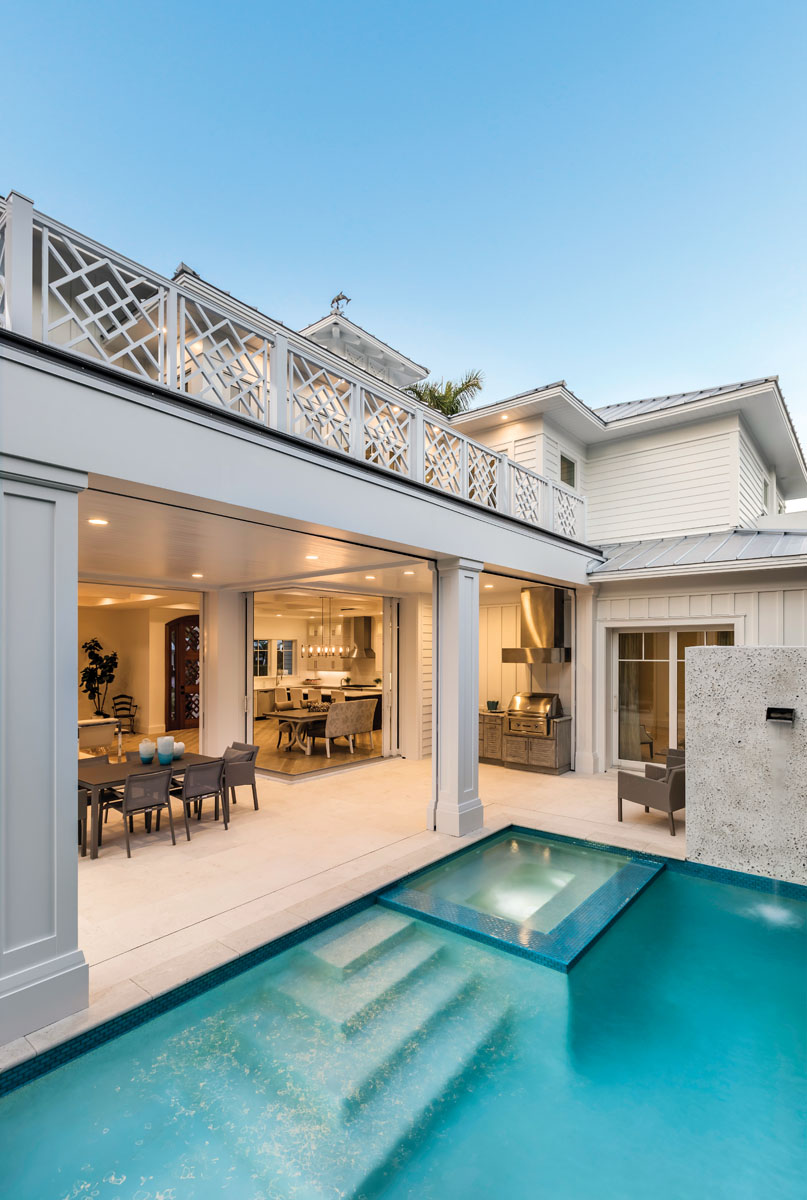 An alluring loggia and pool area offer a breezy oasis for alfresco entertaining and family gatherings. The outdoor living area with a dining table and grill station blend effortlessly with the indoor spaces via large pocketed sliding-glass doors in the kitchen and living room.