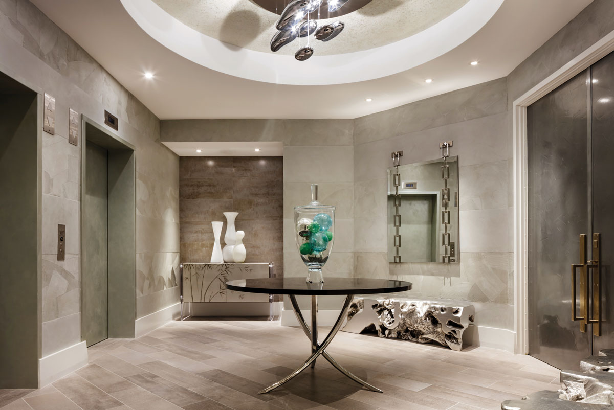 The elevator entry delivers an exciting prelude to the visual treat that lies ahead. The interior scheme is restrained but animated with textured walls, a vibrant chandelier by Artemide, a gleaming center table from Swaim, a metallic free-form bench by Phillips Collection, and white vases atop Theodore Alexander's console.