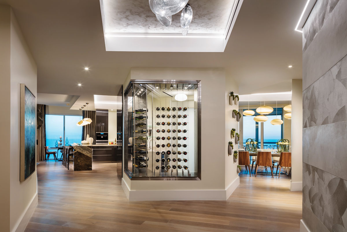 The first glimpse of the Gulf of Mexico is from the hallway anchored by a stainless steel and glass wine room that features a cable bottle display by Michael Zerbe. O'Guin's custom silver-leaf ceiling treatment overhead reflects the glass orbs of a Sonneman light fixture.