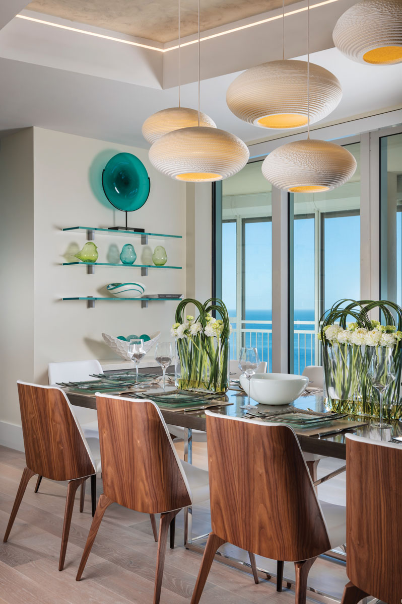 A series of white orb lighting from Graypants creates a playful aesthetic in the dining room. Roberta Schilling Collection's walnut-framed chairs surround Vanguard's high-gloss walnut dining table to style a contemporary yet warm and inviting space.