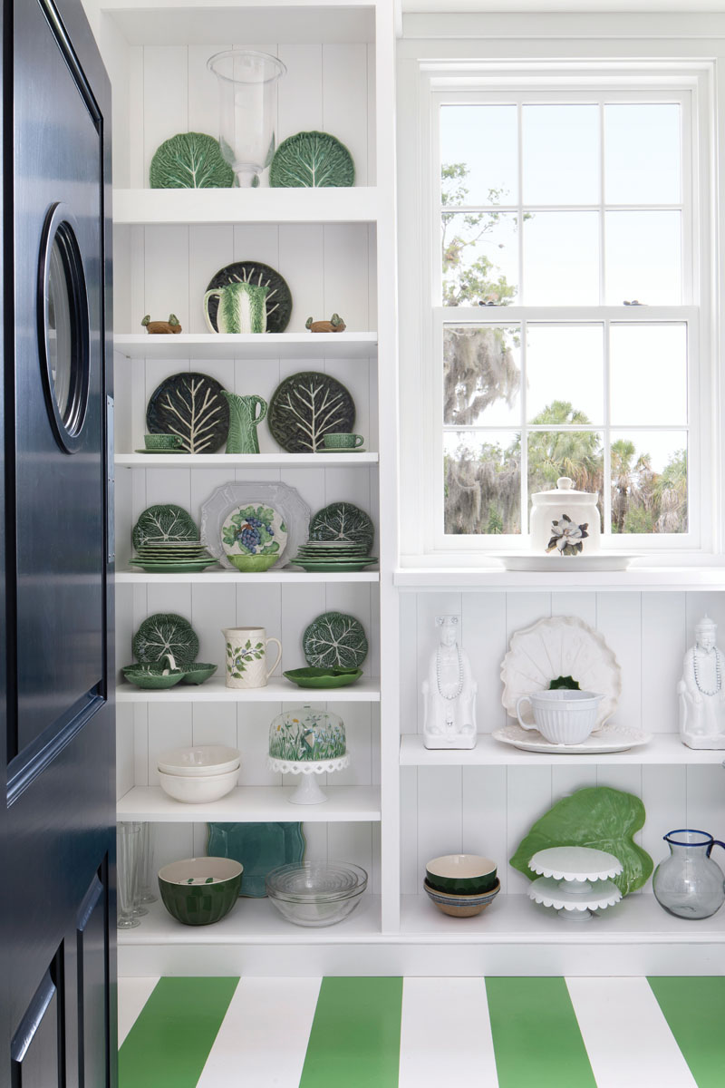"A porthole door swings open to the pantry, where crisp white shelving that displays a collection of green and white serviceware is mindful of age-old butler pantries. The wife's striped ""pickle and white"" flooring strikes a refreshing chord."