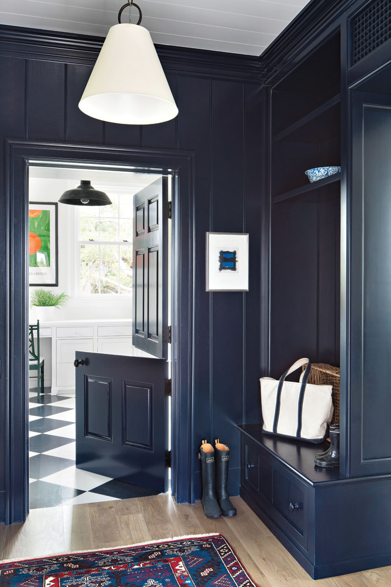 "Equipped with lockers, a quaint bench seat and a fanciful Dutch door, the ""Anchors Away"" blue mudroom gives way to the laundry room. This oversized space supports the children's craft-making activities."