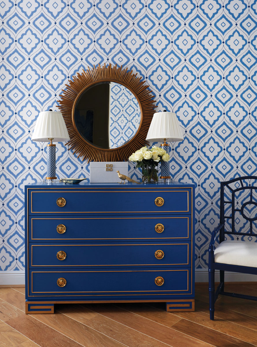 Upon entry, Arteriors' starburst, bronze-framed mirror echoes the metal accents from the Lillian August chest resting beneath A pair of blue lamps from East Enterprises and Bungalow 5's armchair with its window-pane back exude an eclectic flair while subscribing to the home's overall finesse.