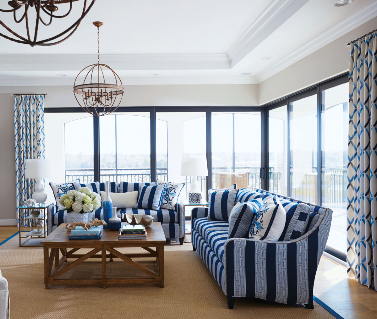 Straight lines and curvy elements continue in the living area, where Zêugma's open-globe chandeliers in an antique-gold finish dangle above CR Laine's sofas in bold stripes.