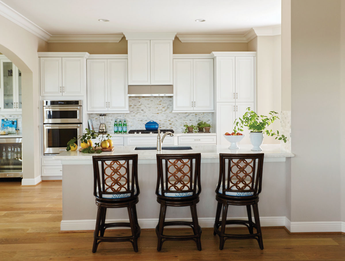 """Artistica's swiveling counter stools draw the eye into the kitchen. A delicate, blue coral reef pattern covers the seats while an intricate, tan rattan weave styles the back. """"The homeowners wanted to keep the kitchen simple and bright with just a touch of color,"""" interior designer Pamela Harvey says."""