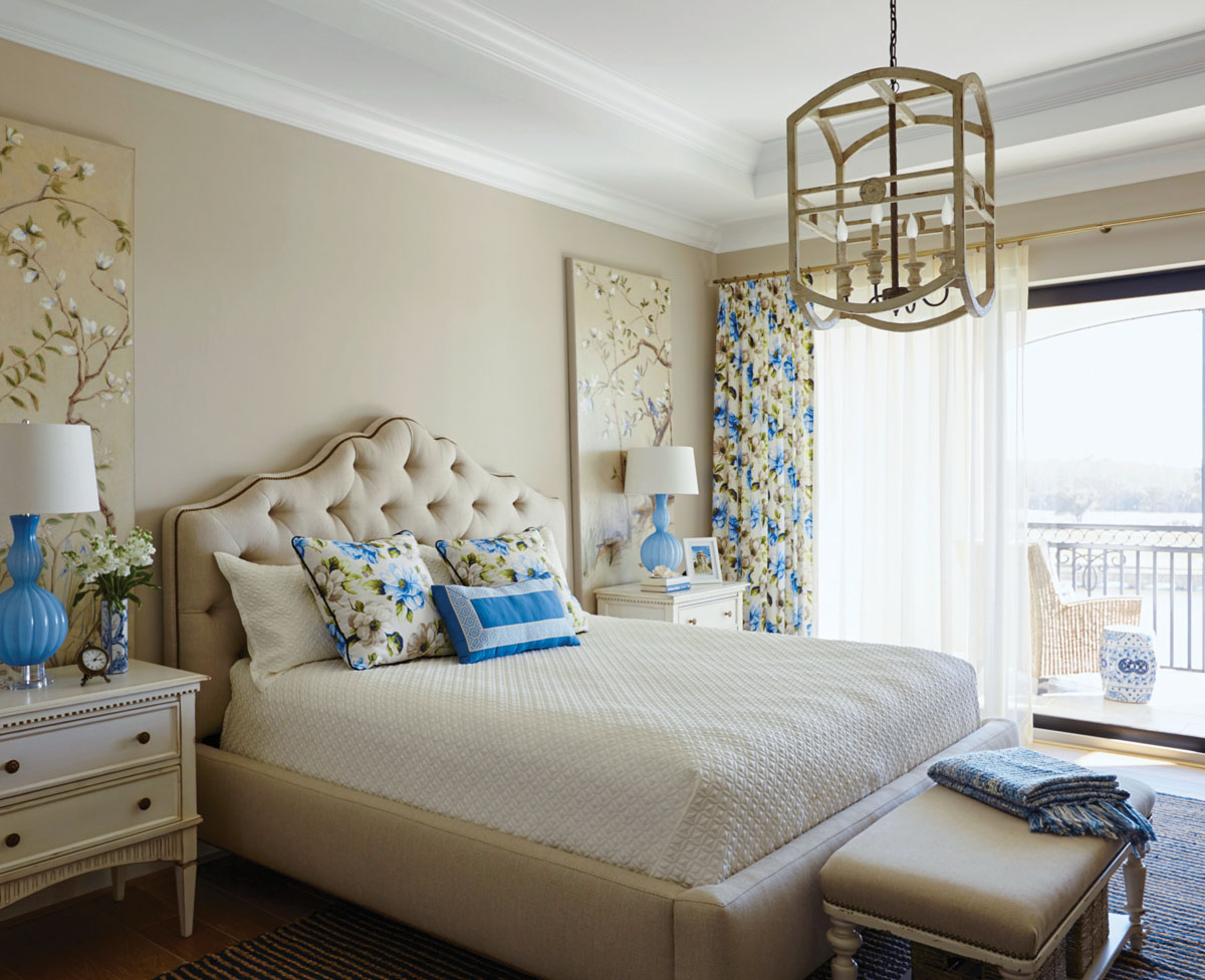 The master bedroom has fun with florals. Blossoming chinoiserie climbs the wall above antique white commodes from Alden Parkes. Stout's blue and yellow print styles the accent pillows and draperies to become an irresistible backdrop that romances the private space.