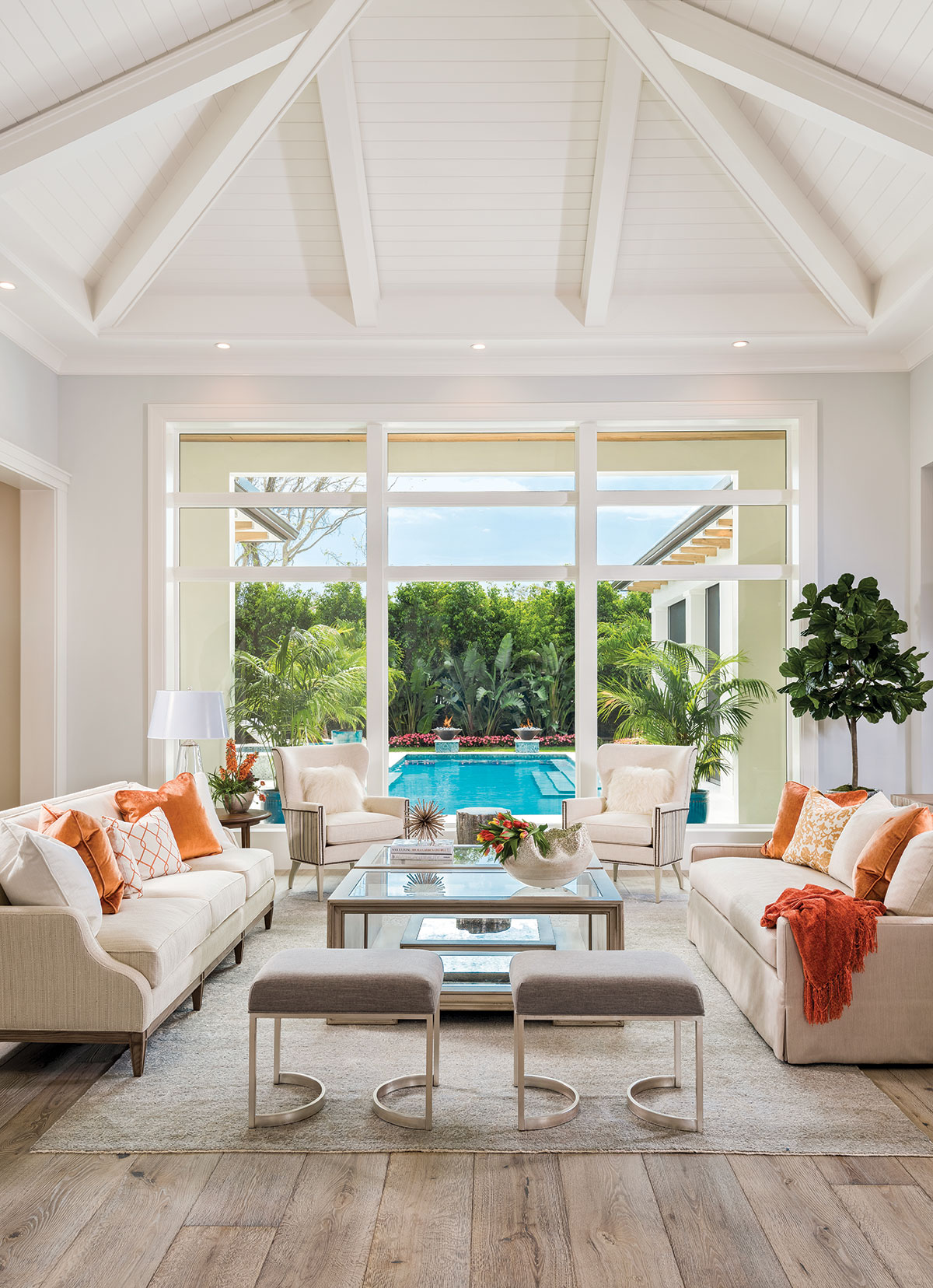 The landscape design surrounding the pool is visible from the great room and affords the home complete privacy. A pair of ivory colored armchairs with sides wrapped in striped velvet and gray-linen ottomans with brushed-nickel bases flank antique cocktail tables from Habersham. A light gray, hand-knotted area rug from Loloi grounds the space in comfort.