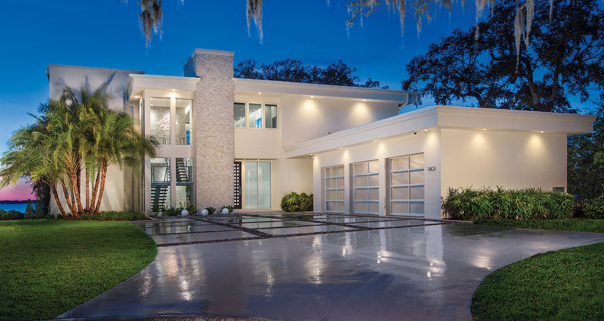 Recessed LED lighting illuminates the exterior of the home, where a floating stairway with a powder-coated steel frame can be viewed through tall, floor-to-ceiling glass windows. A spacious poured concrete drive is patterned in a grid motif.