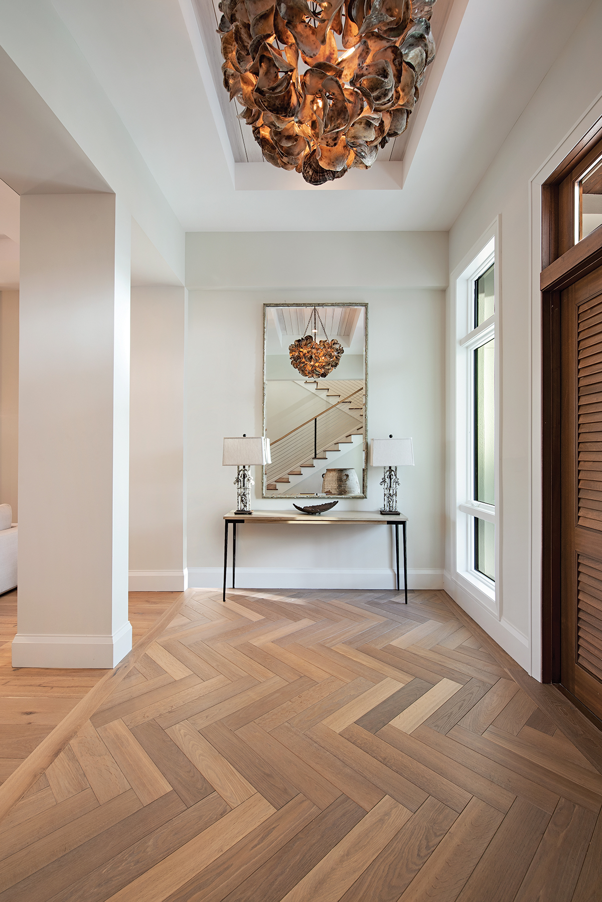 "In the foyer, the ""Venus"" chandelier, a true one-of-a-kind work of art comprised of saddle oyster shells, captivates from above. Legone Bastone's Giuseppina wood planks from Naples Flooring grounds the entry space in a handsome herringbone pattern."