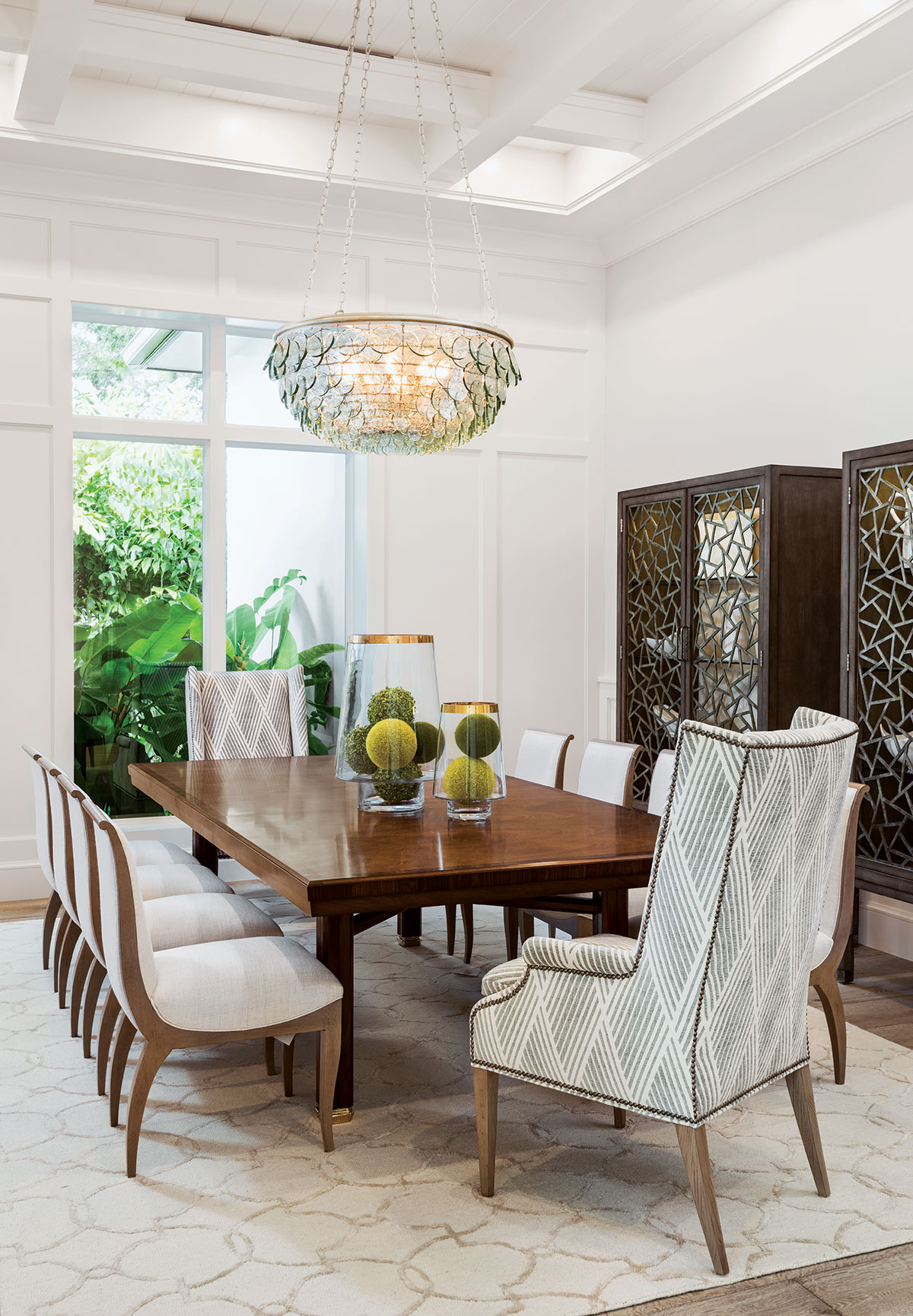 """In the dining room, Hickory Chair's high-back host chairs with nail head trim and side chairs upholstered in crème linen bring formality into the space. """"Many of our clients spend four to six months in Naples, and appreciate having a beautiful space to entertain while enjoying this peaceful lifestyle,"""" design director Debra Lysy says."""
