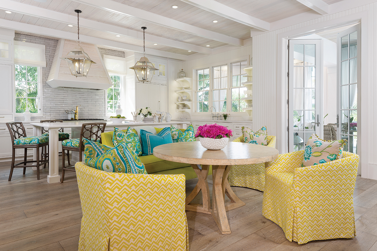 In the breakfast area, yellow-and-white slipcovered chairs from Lee Industries mix with a chartreuse banquette to create a cozy feel. Beyond in the kitchen, two vintage pendants illuminate a white island from Cabaret Cabinetry.