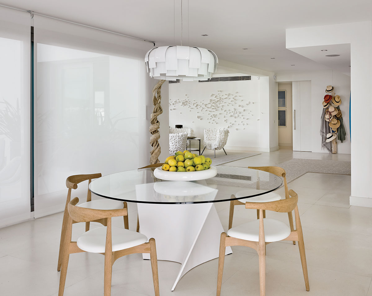"Lovingly called the ""artichoke"" by Poggi, FontanaArte's light pendant brilliantly illuminates the dining area. Here, Zanotta's table base is a swirl of white resin circled by Hans J. Weger's elbow chairs shaped of white oak and seated in leather."