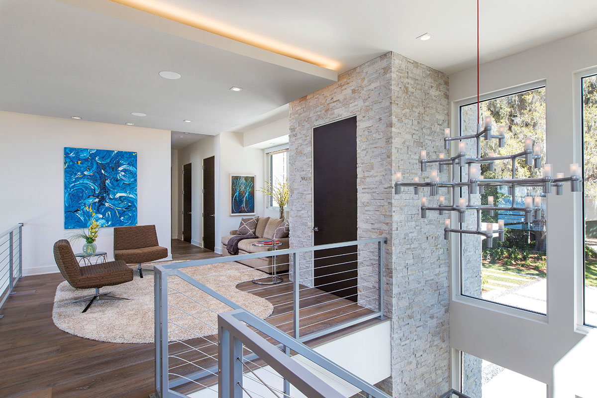 """Upstairs, an intimate sitting area is defined by a shapely area rug. """"Nemo,"""" from YLighting, is a modern interpretation of a classic candle chandelier, that suspends stylishly from the two-story ceiling."""