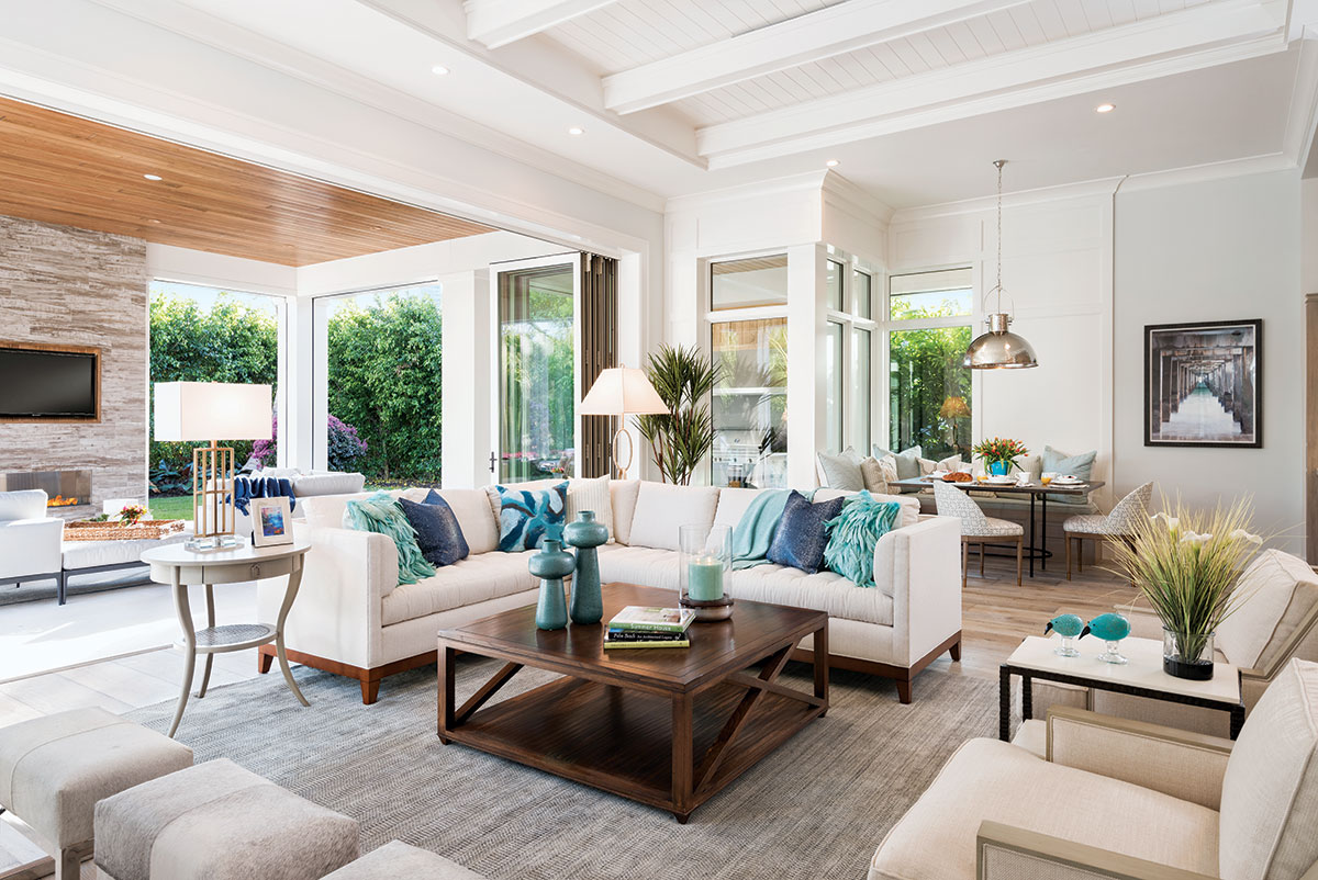 In the comfortable family room with views of the outdoors, a walnut cocktail table from Vanguard is surrounded by a furniture grouping upholstered in cream linen, triple hair-on-hide ottomans with a polished steel base, and a stone and metal occasional table.