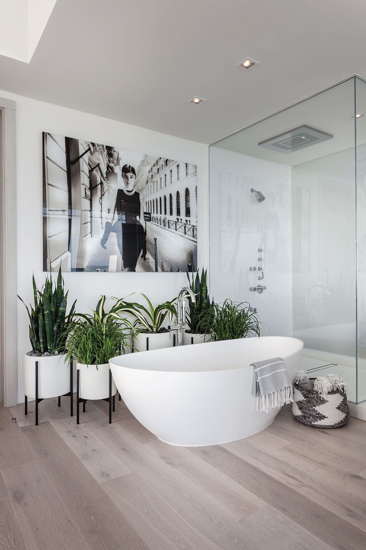 """A large black-and-white photograph of Audrey Hepburn by photographer Axel Crieger keeps watch in the master bath over a vessel tub, a """"rain"""" shower and a collection of lush plants."""