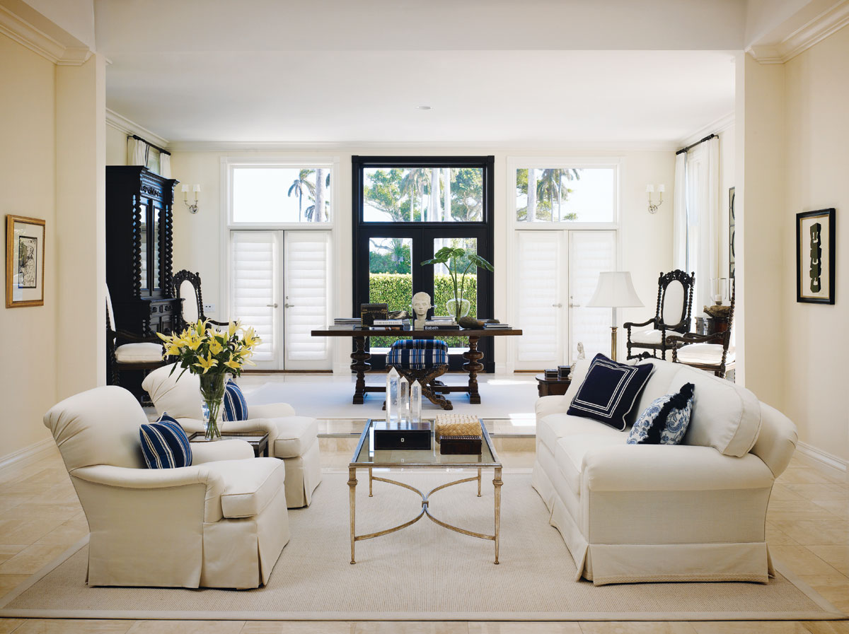 "In the living room, a cocktail table from Nancy Corzine fronts a deep-seated white sofa from Kravet topped with accent pillows clad in Ralph Lauren prints. ""The case pieces were for the most part one-of-a-kind,"" the designer says. ""So that we could create a unique effect that complemented the serenity I wanted."""