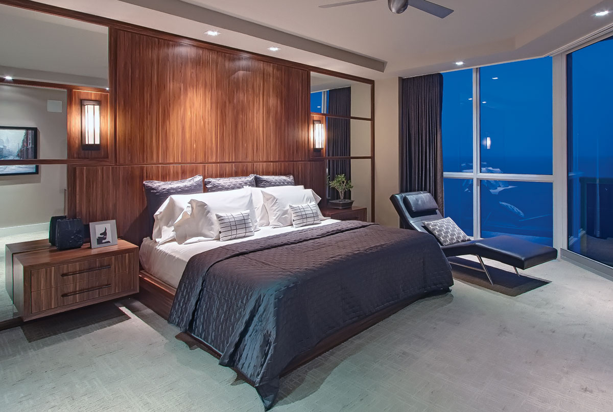 From the master bedroom, the owner wakes to a window scene of rippling aqua-blue water. Custom bedside tables designed by Studio 33 Interiors are set against a dark wood veneer wall that lends a quiet ambiance to the room.