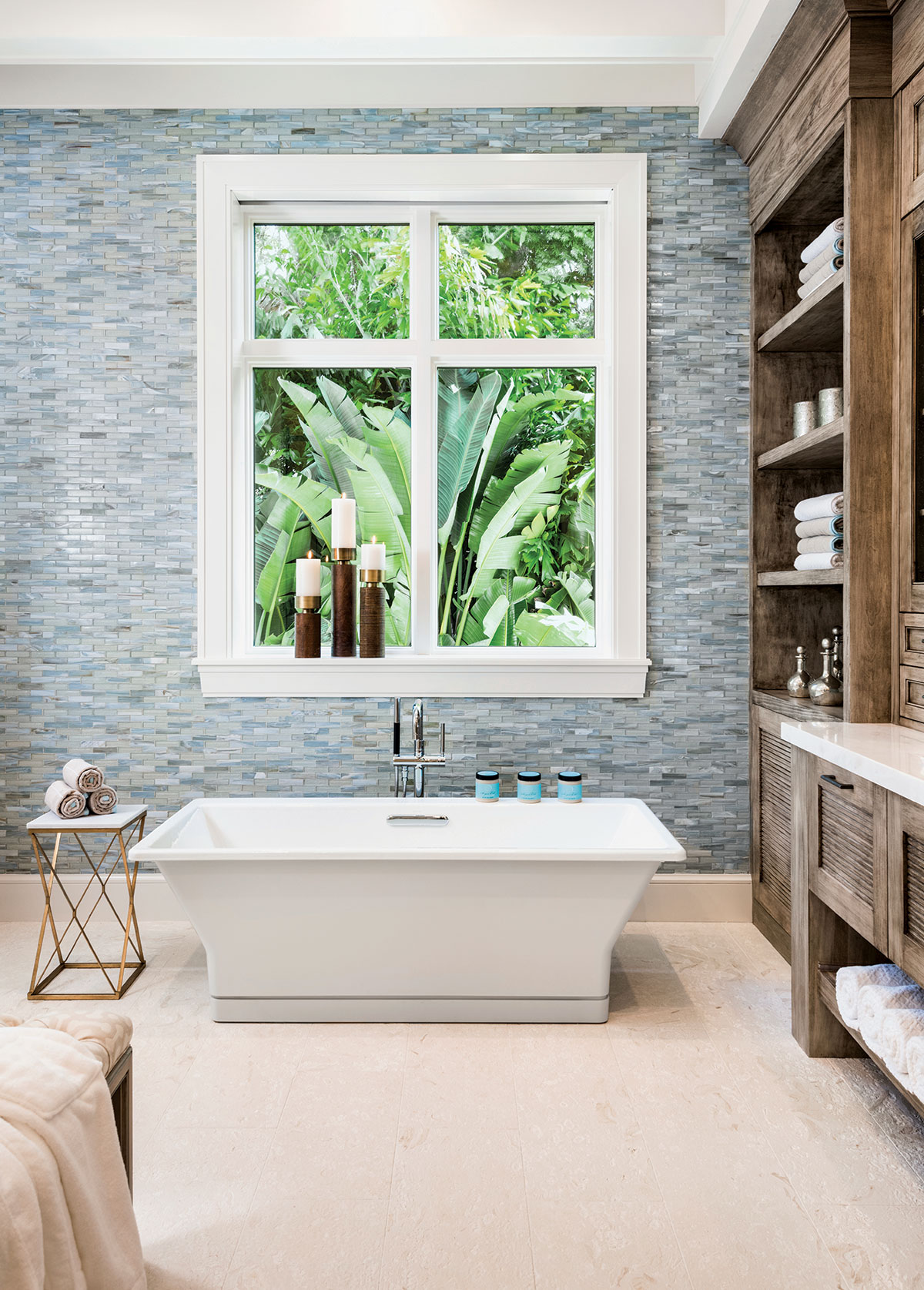 The tranquil, contemporary master bath reflects the homes coastal theme with a glass tile wall in tones of cool pale blue and soft greens. A rectangular vessel sink adds a spa-like vibe.